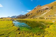 High altitude green alpine lake in autumn season Royalty Free Stock Image