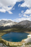 High altitude lake. Deep blue high altitude glacial lake in Yosemite National Park (Tolumne Meadows) with cloudy blue summer sky and snow capped granite stock image