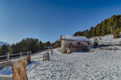High-altitude mountain hut in front of a panorama of snow-capped Royalty Free Stock Photography