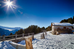 High-altitude mountain hut in front of a panorama of snow-capped Royalty Free Stock Photos