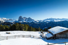 High-altitude mountain hut in front of a panorama of snow-capped Royalty Free Stock Photo