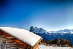 High-altitude mountain hut in front of a panorama of snow-capped. Alpine chalet surrounded by a fence in the snow in front of a panorama of snowy peaks on a Stock Image