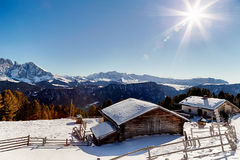 High-altitude mountain hut in front of a panorama of snow-capped. Alpine chalet surrounded by a fence in the snow in front of a panorama of snowy peaks on a Royalty Free Stock Image