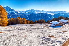 High-altitude mountain hut in front of a panorama of snow-capped. Alpine chalet surrounded by a fence in the snow in front of a panorama of snowy peaks on a Royalty Free Stock Images