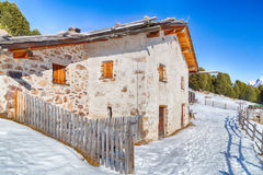 High-altitude mountain hut among snow-capped peaks and pine fore Stock Image