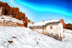 High-altitude mountain hut among snow-capped peaks and pine fore. Alpine chalet surrounded by a fence in the snow among snowy peaks and pine forest on a bright Royalty Free Stock Photography