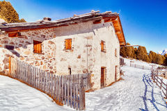 High-altitude mountain hut among snow-capped peaks and pine fore Royalty Free Stock Image
