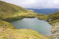 High altitude mountain landscape of a lake surrounded by green hills Stock Photo