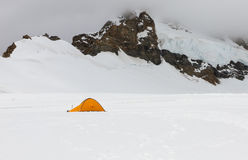 High altitude mountaineering. Mountaineering, adventure, expedtion concept: tent in high altitude alps with snow and glacier, Switzerland Royalty Free Stock Images