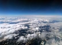 High altitude photograph of the snow covered alps with dark sky and white clouds covering the earth with curved horizon. High altitude photograph of the snow stock photos