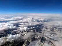 High altitude photograph of the snow covered alps with blue sky and white clouds covering the earth with curved horizon. High altitude photograph of the snow stock photo
