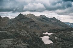 High altitude rocky landscape and little lake. Majestic alpine landscape with dramatic stormy sky. Wide angle view from above, ton. Ed image, vintage filter Stock Photos