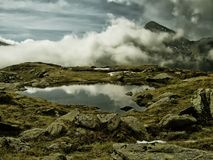 High altitude scenic mountain landscape with mountain lake. Stones,grass,clouds,fog, sky and peak.Sunshine, reflexion on water, mystique  relaxing  nature Royalty Free Stock Image