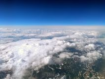 High altitude view of the earth from an airplane with deep blue sky and clouds covering a mountain landscape. A high altitude view of the earth from an airplane royalty free stock photography
