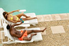 Couple toasting glasses of cocktail while relaxing on a sun lounger near swimming pool. High angel view of cute happy diverse couple toasting cocktail glasses stock photography