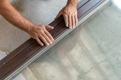 Man holding hands on new window frame. High angle above top view cropped and close up photo of adult handyman holding hands on window frame press two plank royalty free stock photos