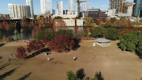 High angle day flyover dog park in Austin Texas. A high angle aerial establishing shot of pet owners playing with their dogs at the Auditorium Shores Dog Park on stock video