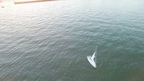 High angle aerial view of yacht sailing away from coast on a bright sunset with sunny flares and rays