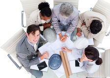 High angle of architects in a meeting. High angle of international architects studying blueprints in a meeting Royalty Free Stock Photos