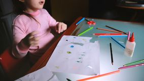 High angle camera sliding right over little Caucasian girl child in pink sweater drawing with colorful pencils at table. stock footage