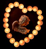 High-angle close-up of a vintage angel figurine. High-angle close-up view of a vintage angel figurine in a heart shape made of burning prayer candles on dark stock images