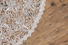 High angle closeup shot of the lace train of a wedding dress on the wooden floor