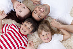 High angle of family on floor with heads together Stock Image