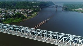 High angle flyover coal barge on Ohio river. 10295 An early morning high angle flyover of a barge traveling on the Ohio River under a bridge. Side motion stock video