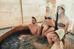 Group of caucasian diverse friends enjoying jacuzzi in hotel spa. High angle of happy cheerful people visiting bathhouse in holidays, being overjoyed and happy royalty free stock image