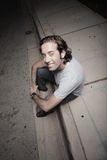 High angle image of a man sitting on a curb Stock Photography