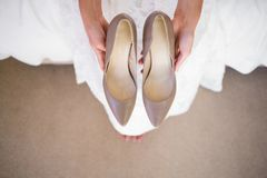 Low section of bride holding shoes while sitting in fitting room. High angle low section of bride holding shoes while sitting in fitting room Stock Images