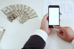 High-angle of man using smartphone in office with money on working desk stock photography