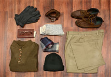 High Angle Mens Clothes. High angle shot of men's winter clothes laid out on a dark wood floor. Items include, Sweater, Scarf, Gloves, wool Socks, Pants, Boots Stock Image