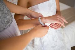 Midsection of bridesmaid dressing bride in fitting room. High angle midsection of bridesmaid dressing bride in fitting room Royalty Free Stock Photo