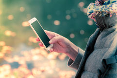 A high angle photo of a brunette woman walking in the park while using a smartphone, lake in the background. Soft focus, dreamy look. Blank smartphone screen Stock Image