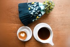 High Angle Photo Of Mug Filled With Coffee Beside Bobble Hat Stock Photo