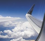 High-angle Photograph of Airplane Wings Above the Clouds Under Clear Blue Sky Stock Photography