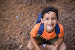High angle portrait of boy sitting in forest Stock Image