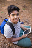 High angle portrait of boy sitting with tablet PC in forest Royalty Free Stock Image