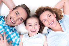High angle portrait of caucasian happy smiling young family. With two children lying down on white floor and looking at camera Royalty Free Stock Image