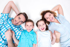 High angle portrait of caucasian happy smiling young family. With two children lying down on white floor and looking at camera Royalty Free Stock Images