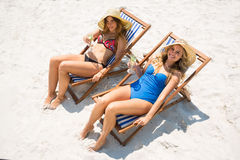 High angle portrait of female friends relaxing on deck chair Stock Photos