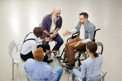 Support Group Circle. High angle  portrait of handicapped men sharing troubles with support group during therapy session, copy space royalty free stock image