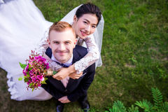 High angle portrait of happy wedding couple standing on grassy field Stock Images