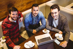 High angle portrait of male friends with laptop. At restaurant Stock Photography