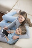High angle portrait of mother and son with tablet PC sitting on sofa Royalty Free Stock Photos