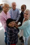 High angle portrait of senior friends stacking hands. While standing in art class Royalty Free Stock Image