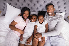 High angle portrait of smiling family lying together on bed Royalty Free Stock Photography