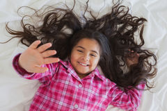 High angle portrait of smiling girl lying in bed Stock Photos