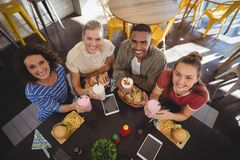 High angle portrait of smiling young friends sitting with lunch at coffee shop Royalty Free Stock Photo